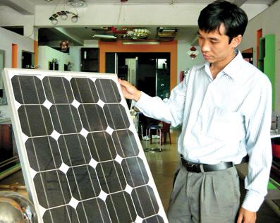 Anh Bùi Văn Nam bên tấm bảng pin mặt trời, sản phẩm mà anh kỳ vọng nhiều trong tương lai.